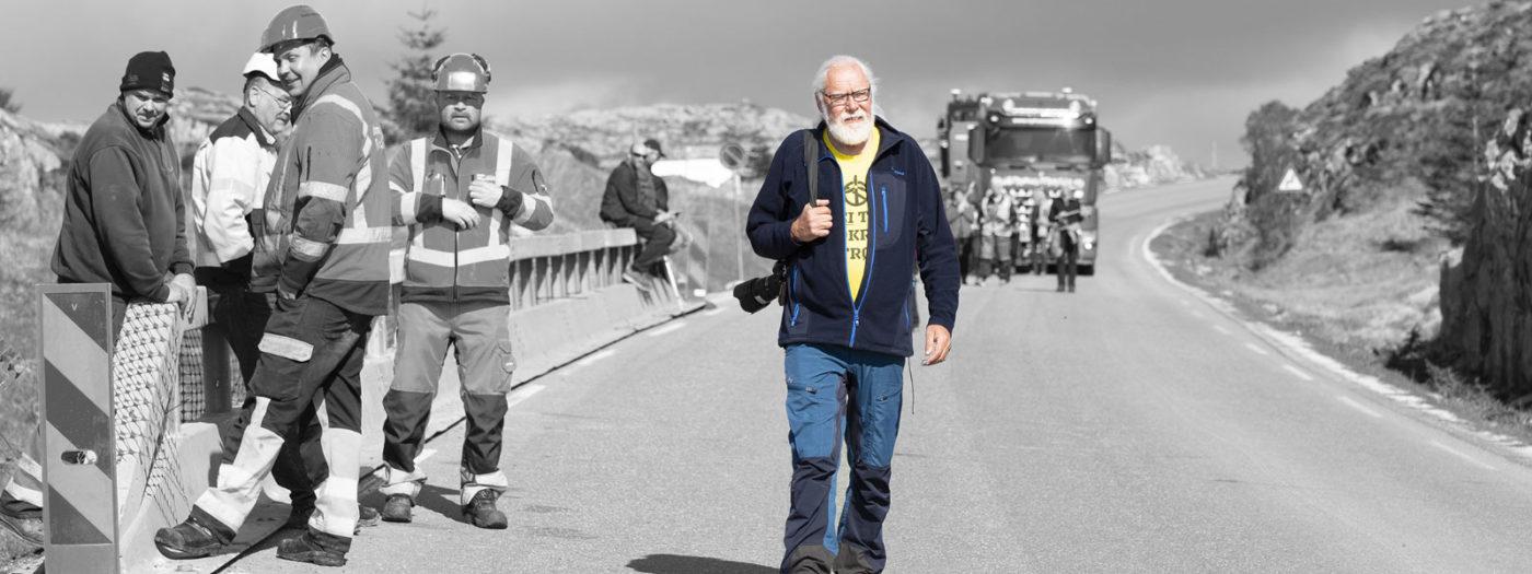 Mann går på veien med anleggarbeidere og tunge kjøretøy i bakgrunnen