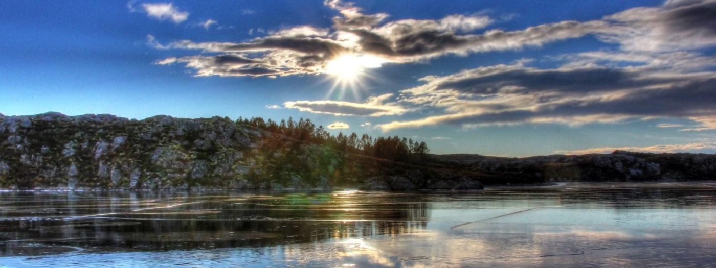 Vann med islag og solen som skimter igjennom